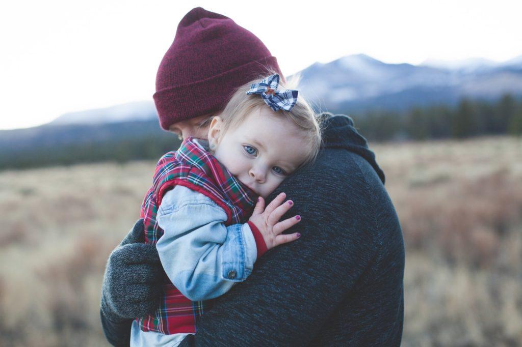 Tata przytula dziecko, w tle jesienny górski krajobraz /Ilustracja do tekstu: Prawa ojca w opiece nad dzieckiem. Urlop tacierzyński, urlop rodzicielski, urlop wychowawczy