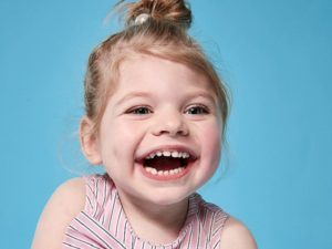 """Uśmiechnięta dziewczynka z zespołem Grouchy'ego /River Island - kampania """"Labels Are for Clothes"""""""