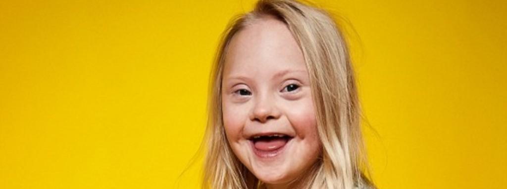 """Uśmiechnięta dziewczynka z zespołem Downa na żółtym tle / River Island - kampania """"Labels Are for Clothes"""""""