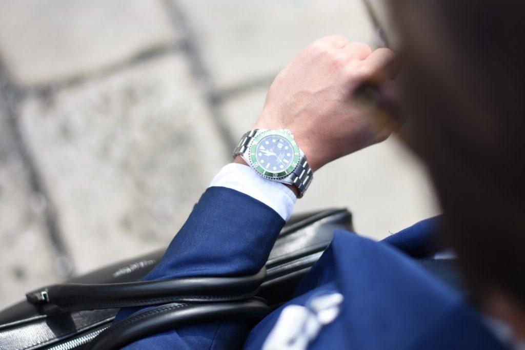 Bizneswoman w garsonce spogląda na zegarek /Ilustracja do tekstu: Godzina dla rodziny: krótszy tydzień pracy dla rodziców