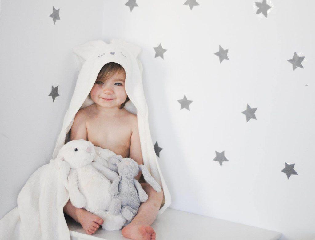Niemowlę owinięte białym ręcznikiem-króliczkiem Samiboo /Ilustracja do: Ręcznik-króliczek uprzyjemni dziecku kąpiel