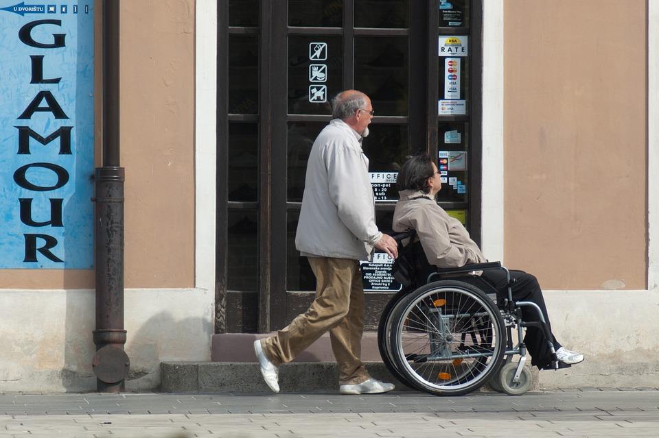 Mężczyzna prowadzi wózek inwalidzki, w którym siedzi kobieta /Ilustracja do tekstu: Protest rodziców osób niepełnosprawnych trwa. Gdzie jesteśmy my, obywatele?