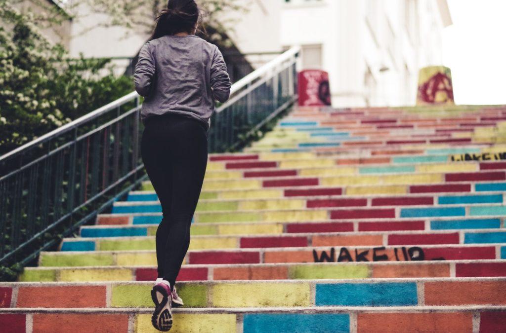 Kobieta w stroju sportowym biegnie w górę kolorowych schodów /Ilustracja do tekstu: Trening biegowy latem - o czym pamiętać?