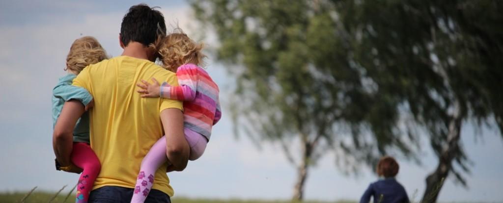 Tata z dwójką dzieci na rękach idzie przez pole maków /Ilustracja do tekstu: Projekt Kodeksu rodzinnego zwiekszy ochronę nad dzieckiem. A co z matką?