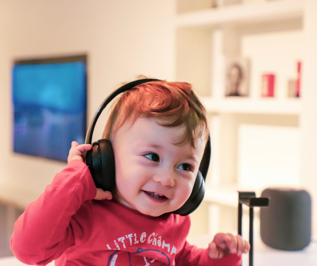 Mały, uśmiechnięty chłopczyk w słuchawkach