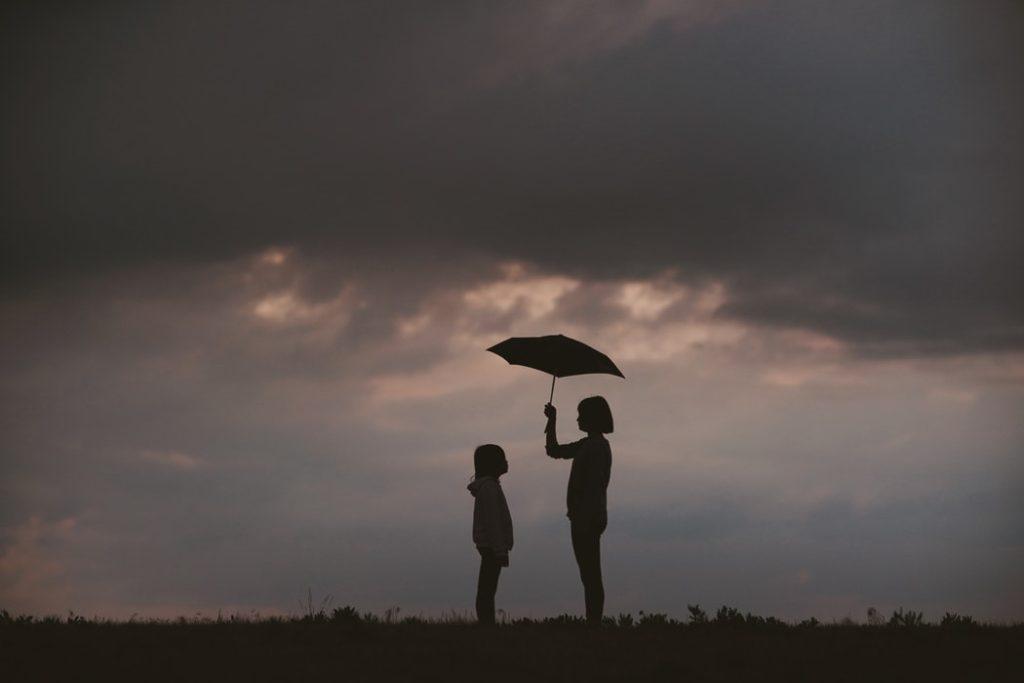Dorosła kobieta trzyma czarny parasol nad głową dziecka w burzowy wieczór /Ilustracja do tekstu: Prewencja samobójstw okiem ekspertów. Światowy Dzień Zapobiegania Samobójstwom