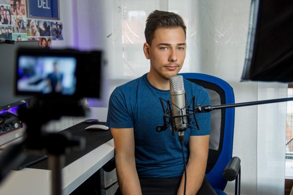 Pasja na pełen etat, czyli jak zostać blogerem i odnosić zyski z bloga /Na zdjęciu: Ok. 2-letni mężczyzna w pokoju; siedzi przed mikrofonem i patrzy prosto w kamerę