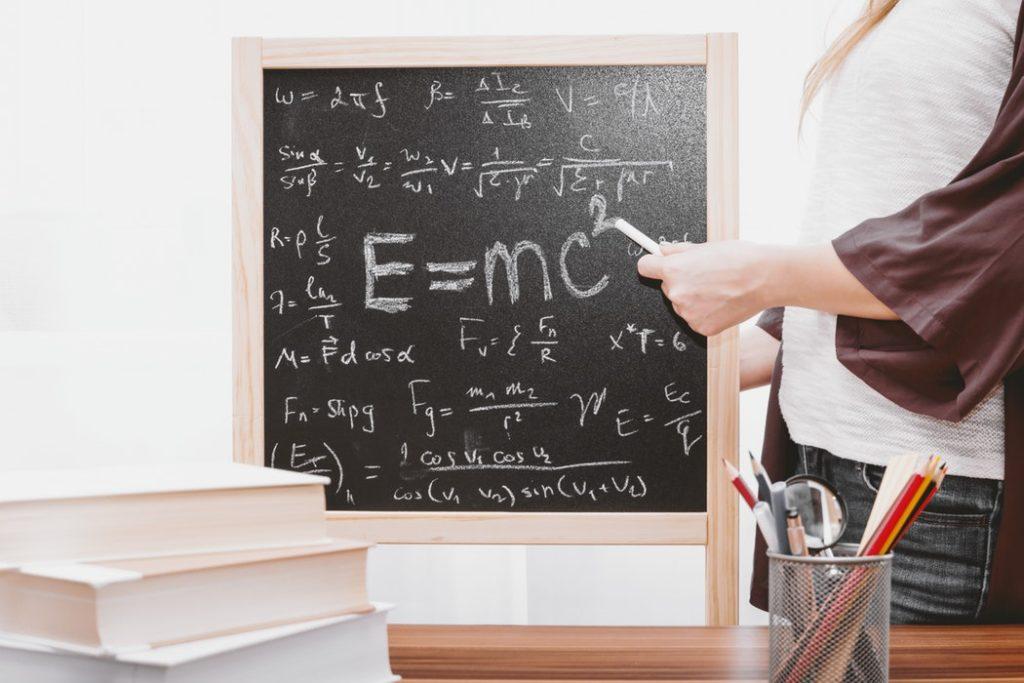 Autorytet nauczyciela spada. Czy można to zmienić? /Na zdjęciu: Nauczyciel wskazuje na tablicy napisany kredą wzór: e=mc2