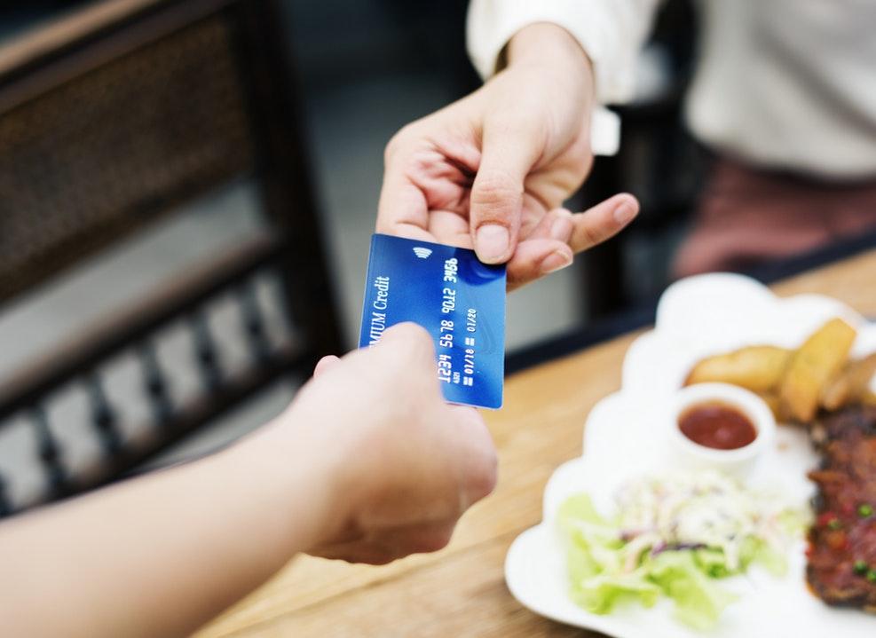Na zdjęciu widać dłoń podającą kartę kredytową pracownikowi kawiarni /Długi pokolenia Y i Z. Tarapaty na raty