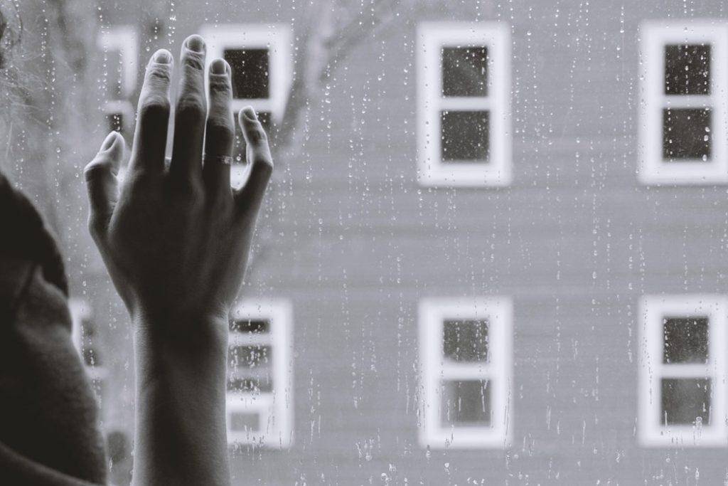 Czarno-białe zdjęcie. Kobieca dłoń dotykająca szyby; widok na blok mieszkalny /Ilustracja do tekstu: Ryzyko samobójstwa wzrasta w święta. Jak pomóc bliskim, którzy doświadczają kryzysów psychicznych?