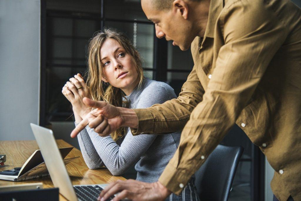 Wypalenie zawodowe: przyczyny, objawy, przeciwdziałanie /Na ilustracji: Dwójka pracowników (kobieta i mężczyzna) dyskutuje nad laptopem