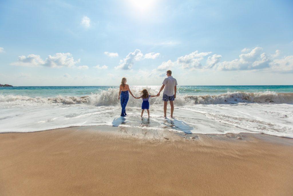 Rodzina z dzieckiem na plaży /Ilustracja do tekstu: Szczepienia przed podróżą: które obowiązkowe, które dodatkowe? Wyjaśnia lekarz